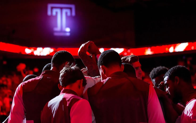 Temple Men's basketball player stand in huddle with arms raised