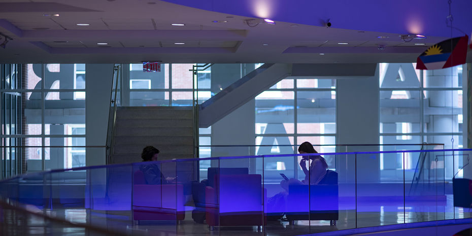 Business students studying together in a blue-lit lobby space