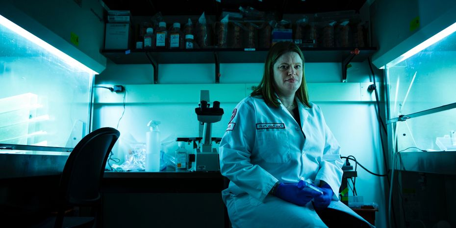 Laura Burdo wearing a lab coat and sitting on a stool in her lab