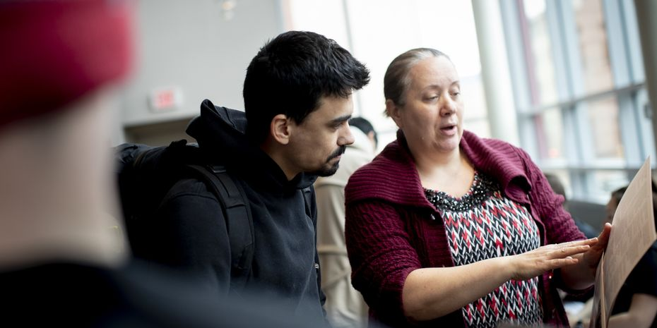 A Temple student discusses a research plan with a faculty member.