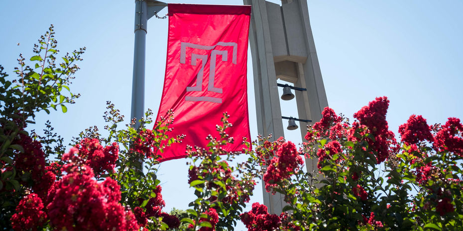 The cherry red Temple T flag waves in front of the bell tower on Polett Walk