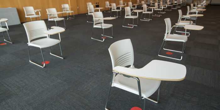 Classroom with red circles on the ground that designate physically distant desks
