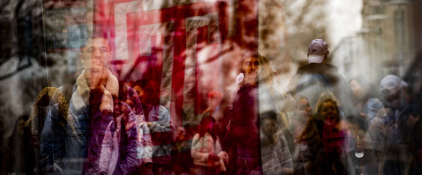 An abstract photo of the cherry Temple T flag overlay with students in the background