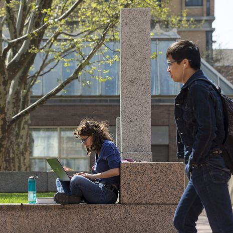 A student sits reading on a wall on a sunny day. Another student is walking by her.