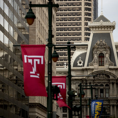 Cherry red Temple T flags line North Broad Street in front of Philadelphia City Hall