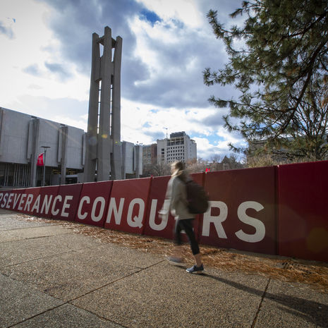 A student walks by a banner that says 'Perseverance Conquers.'