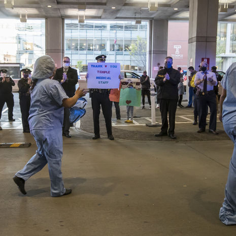 Temple University Hospital medical workers are cheered on by university police officers