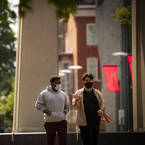 Two masked Temple students talking on Polett Walk