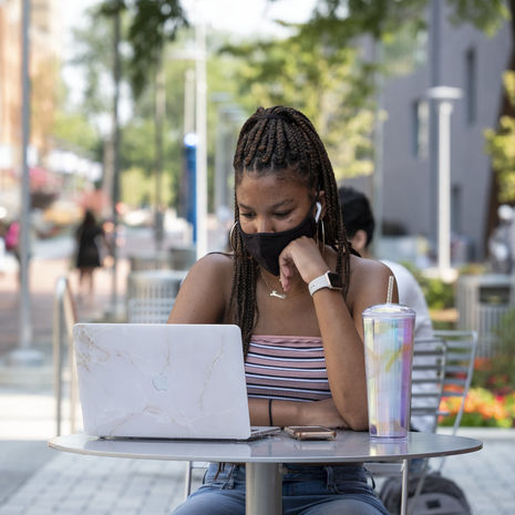 A Temple student sitting at an outdoor table and working on her laptop