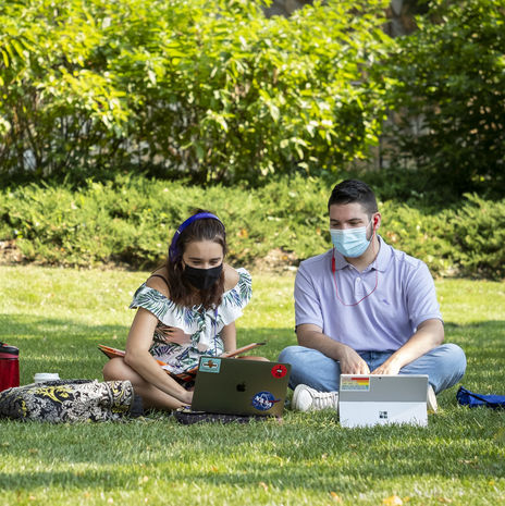 Two masked students sitting on grass and working on laptops on Main Campus