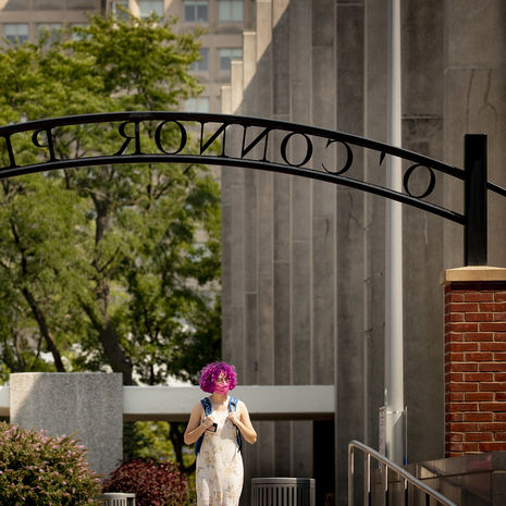 A student with pink hair and wearing a backpack walks through O'Connor Plaza on Main Campus