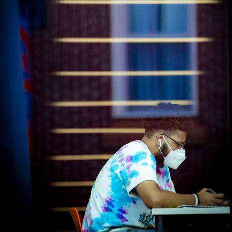 A masked Temple student sitting and studying outdoors