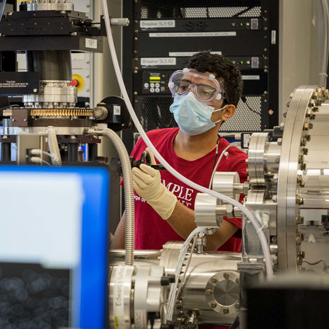 A masked Temple students works in a physics lab