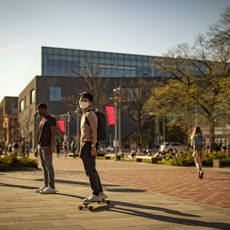 Temple students on Liacouras Walk outside of Charles Library.