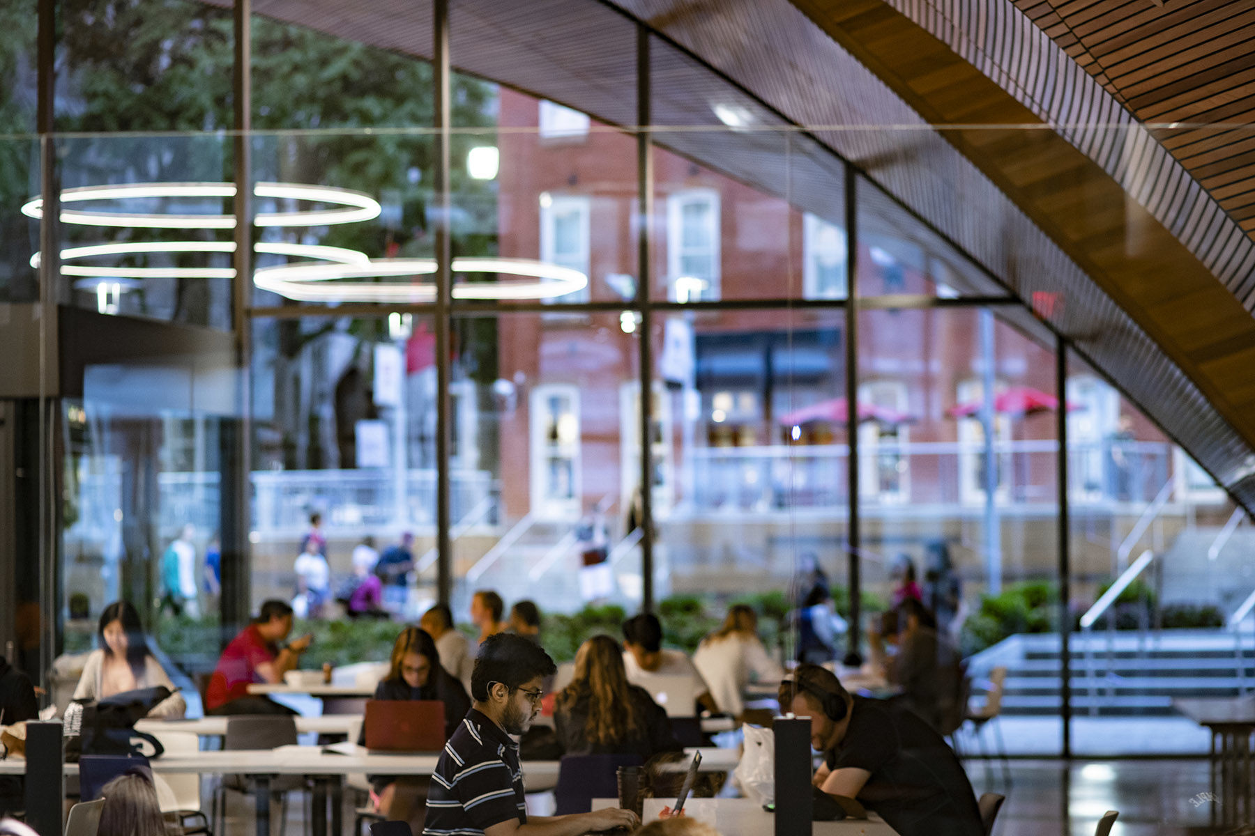 students studying in Charles Library with windows facing out to Liacouras Walk