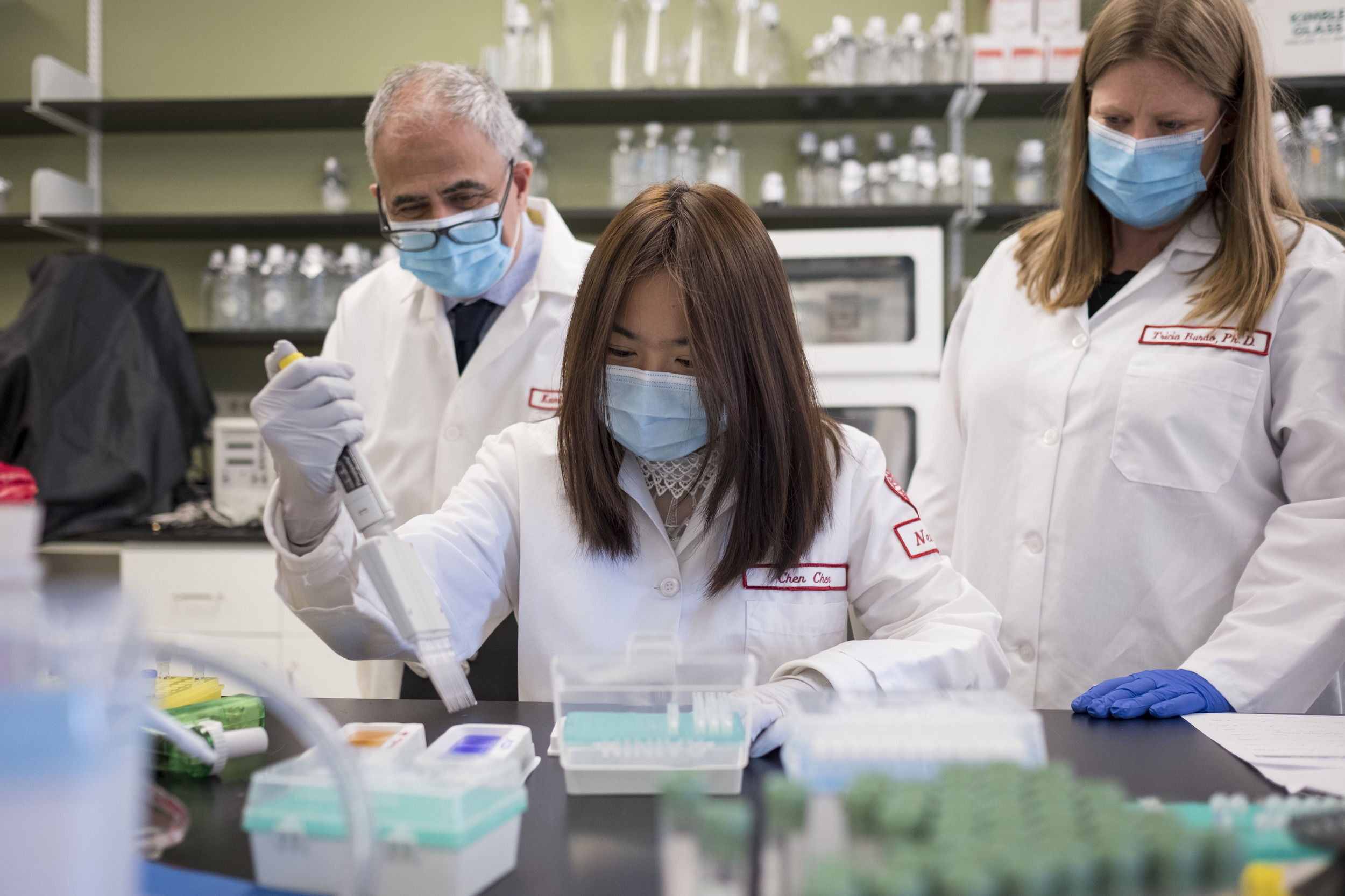 Three researchers wearing white lab coats and wearing masks work together in the lab