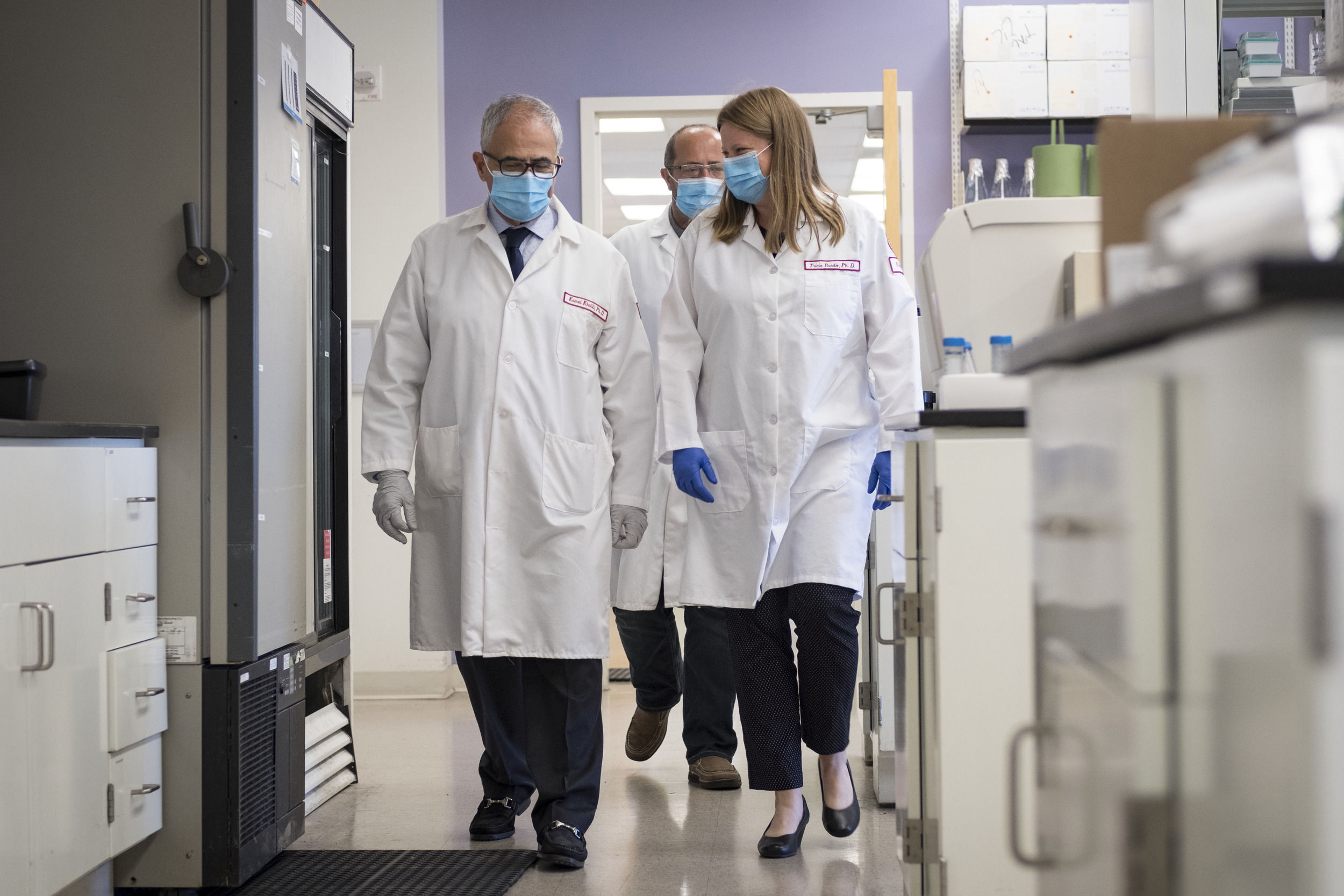 Three people wearing white lab coats and masks walk through the HIV research lab