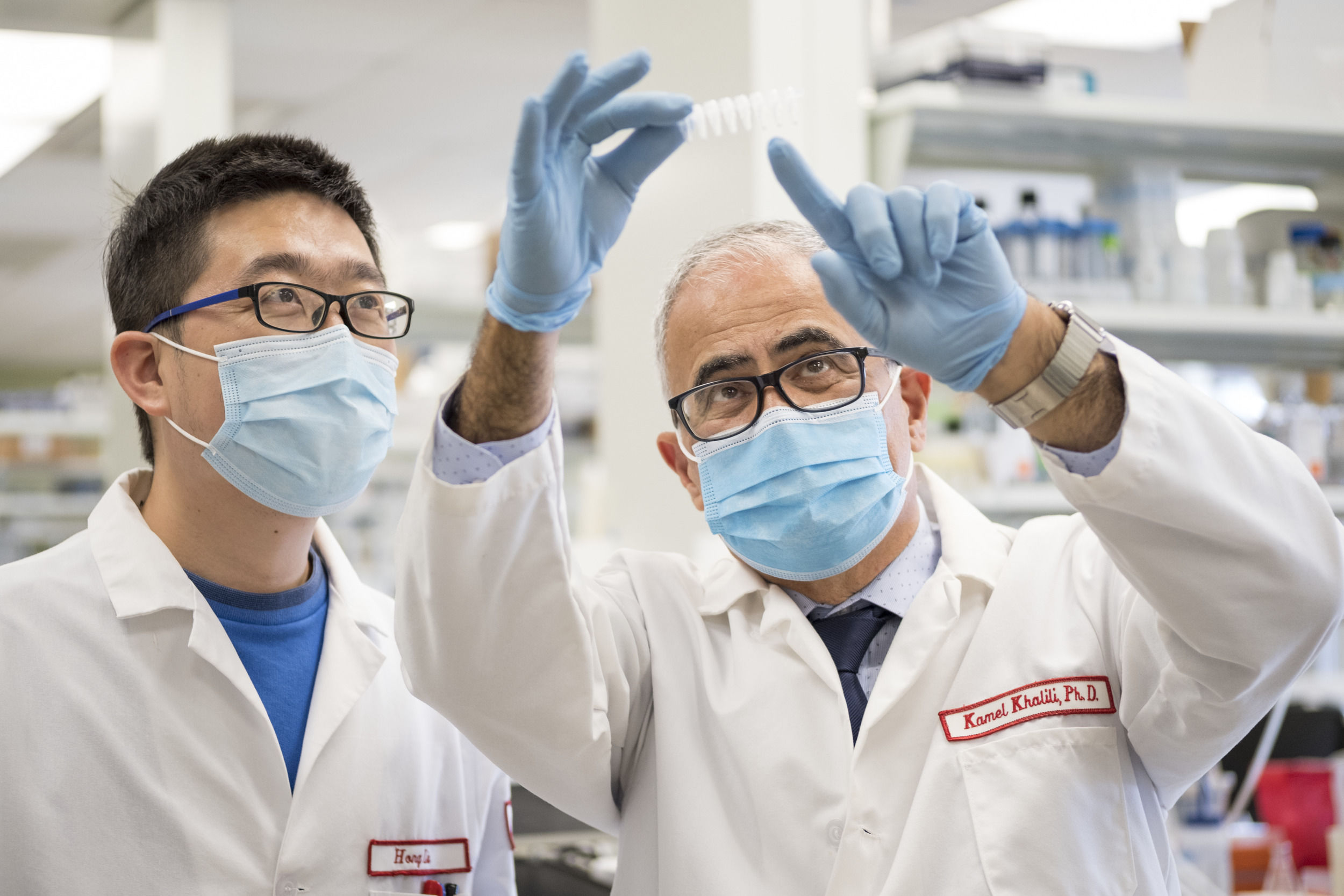 Two mean wearing gloves and masks in the lab