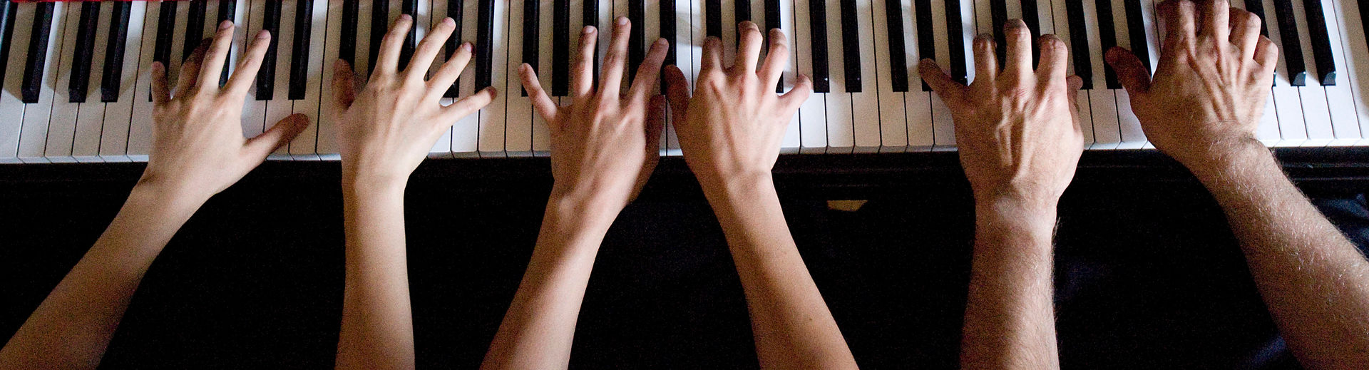 Three pairs of hands playing the piano