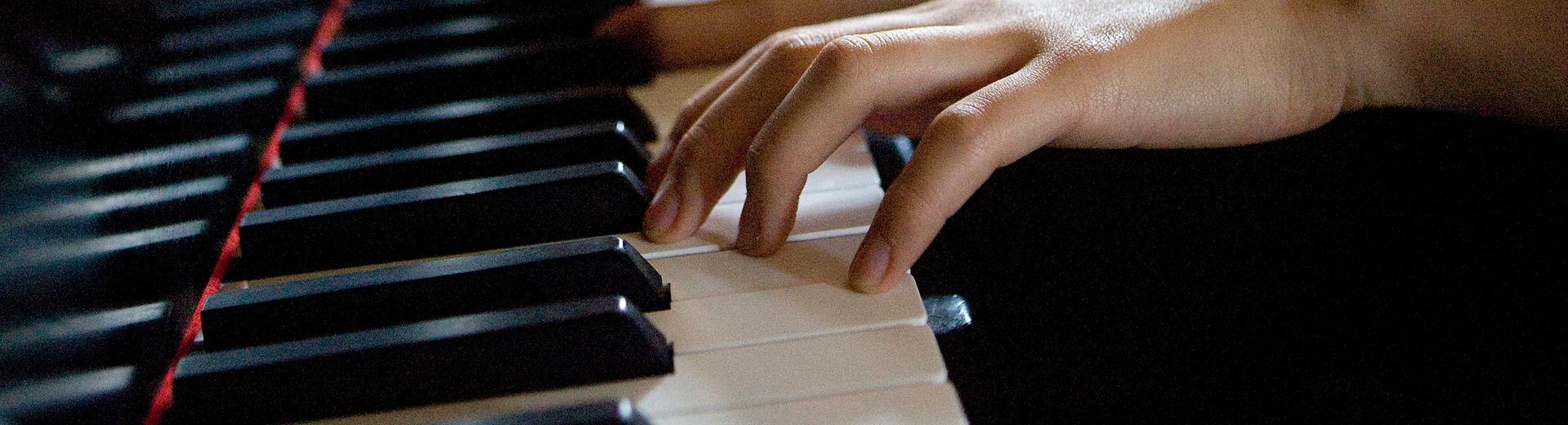Six hands on piano keys playing a song