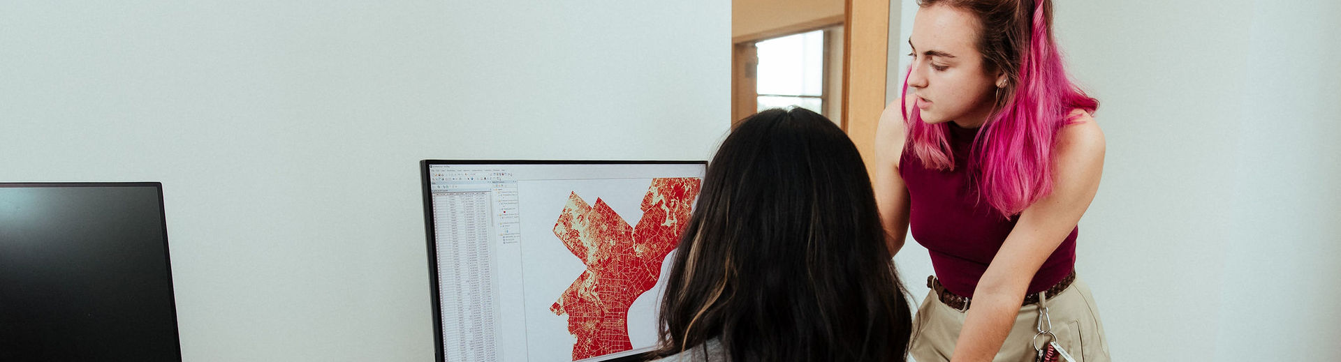 Two students work with GIS software on a computer.