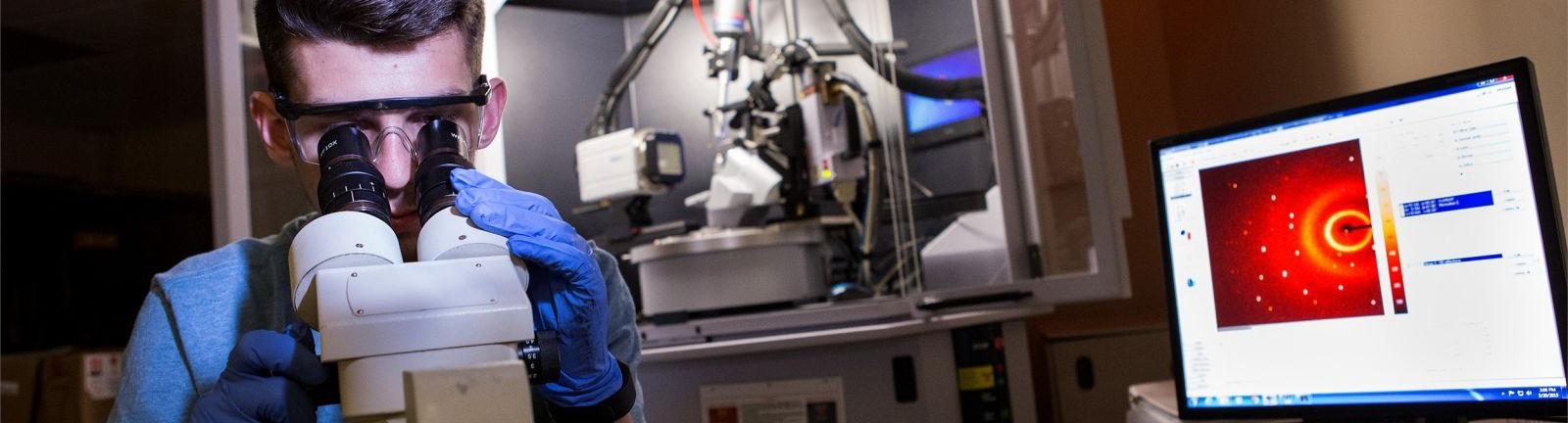 Chemistry student looking through a microscope in a lab surrounded by computer and equipment.