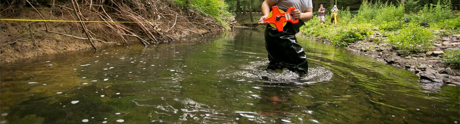 Temple environmental studies student standing in a creek in the woods performing an experiment.