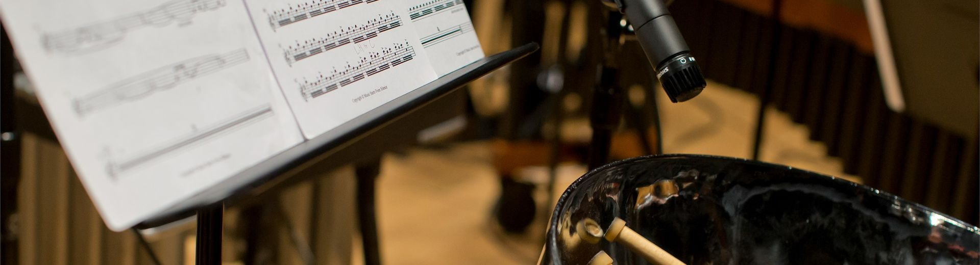 Student playing and recording the drums with sheet music