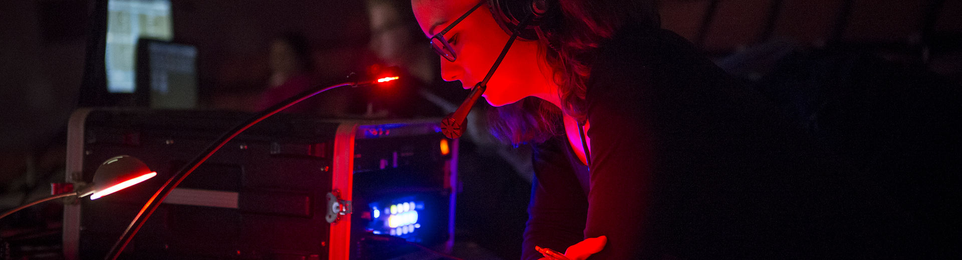 A woman with a headset reads in a darkened room backstage.