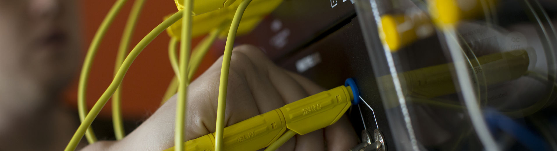 Close-up image of a students hand manipulating wires on a control board