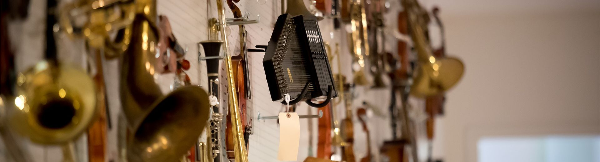 Photo of different musical instruments hanging on a wall.