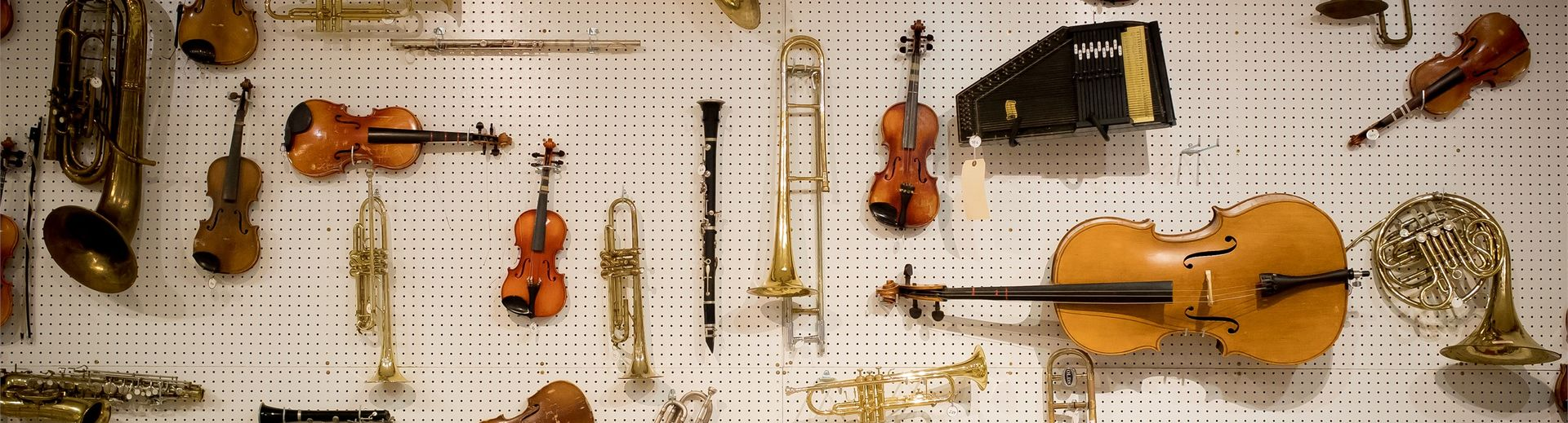 Many different instruments hanging on a pegboard wall.