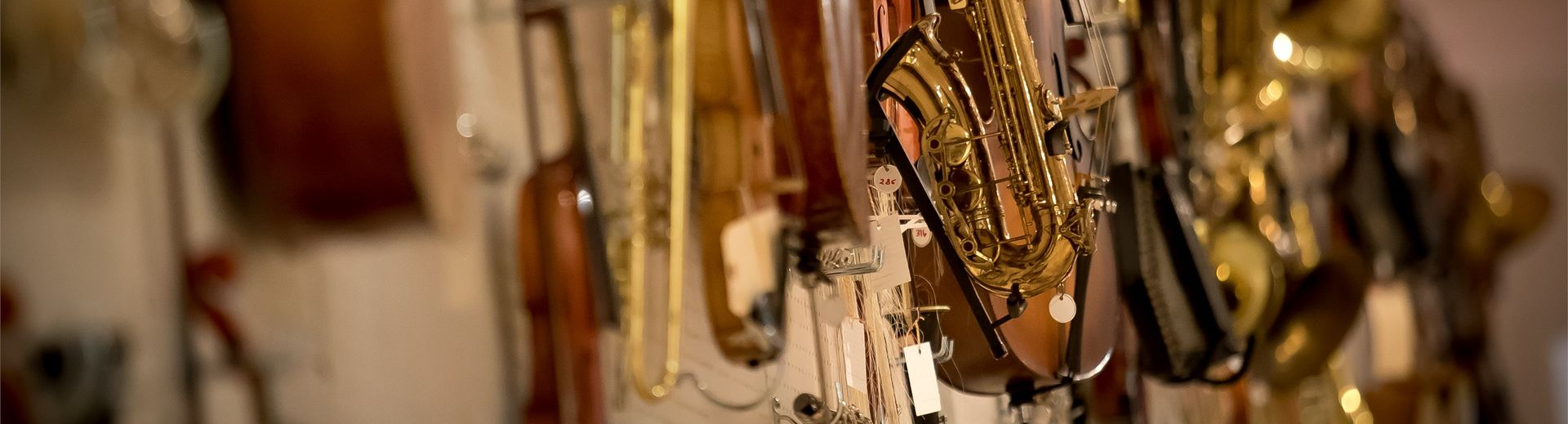 Several string and brass instruments hanging on a wall.