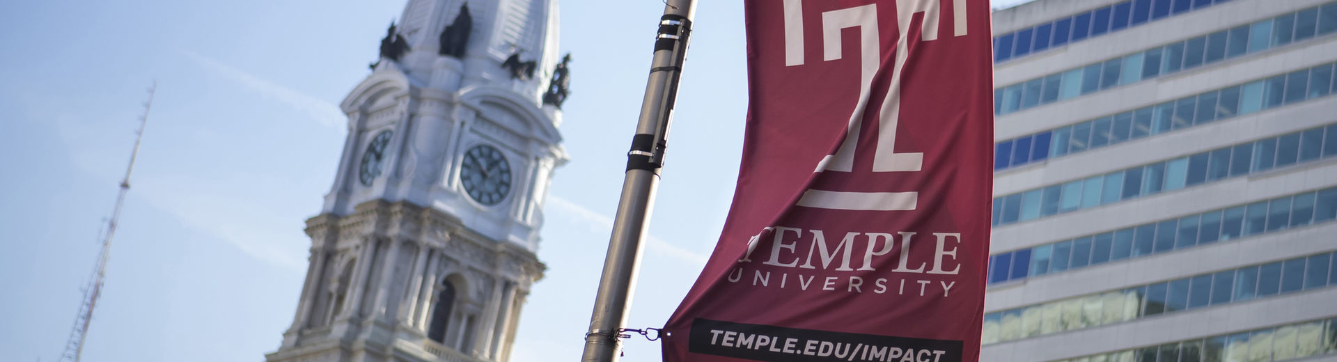 The Temple cherry T flag waves in front of the Philadelphia City Hall building
