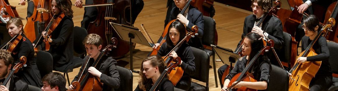 A student string orchestra is shown mid-performance. All musicians are dressed in formalwear.