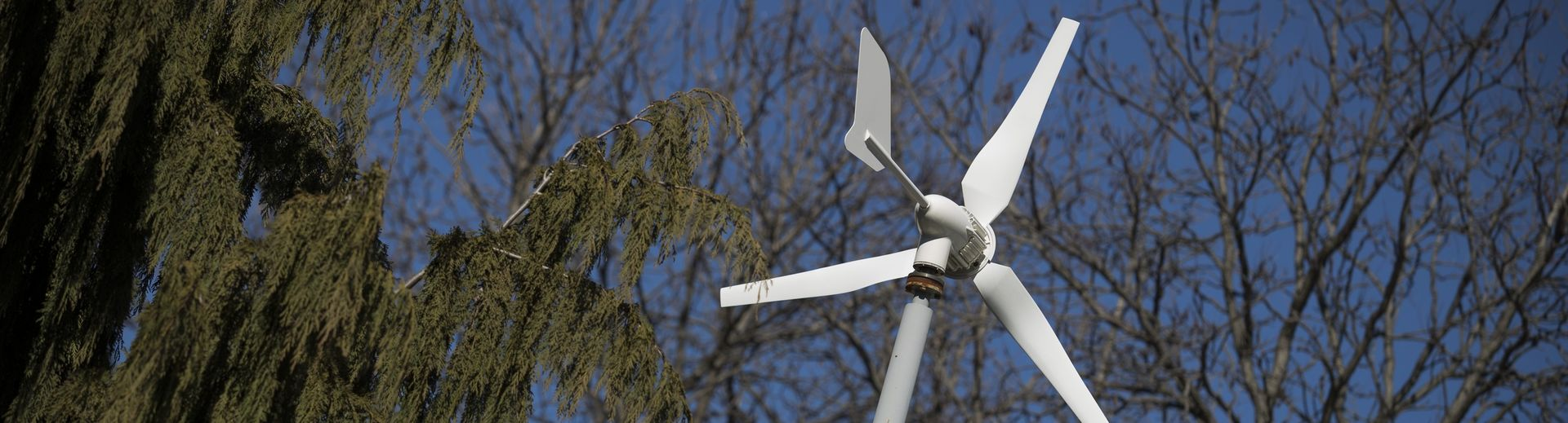 A wind turbine and a sunny, blue sky.