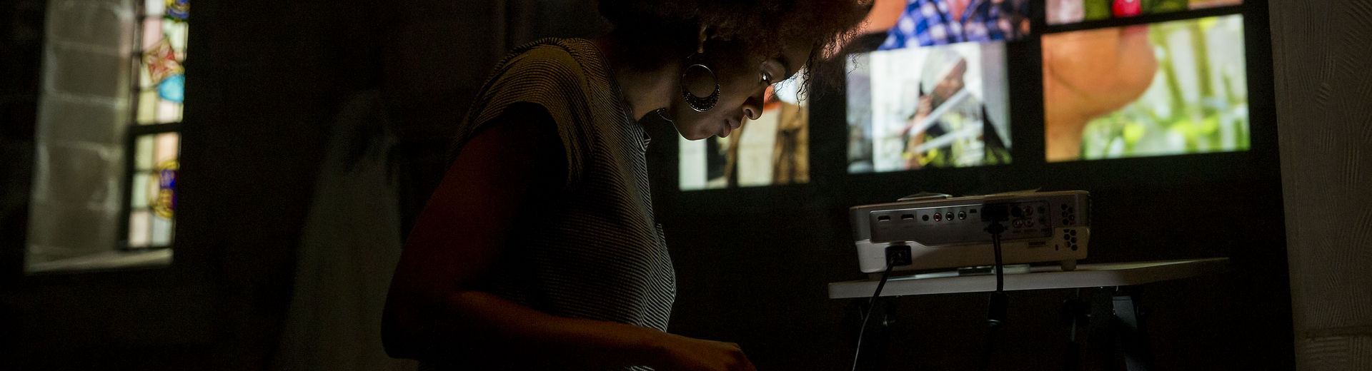 Woman looking at a screen with projected images behind her on a wall.