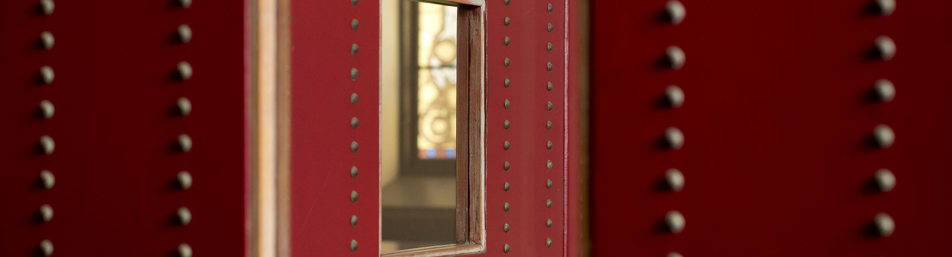 A close up of a mirror within a red frame and a wall laden with studs.