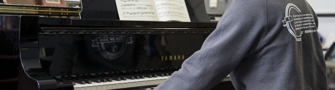 A Temple University student playing a piano.