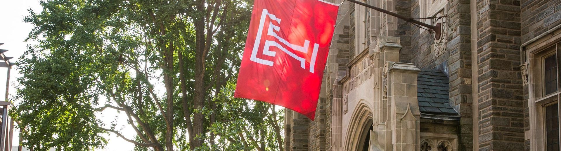 Temple University flag hangs from a historic building on campus.