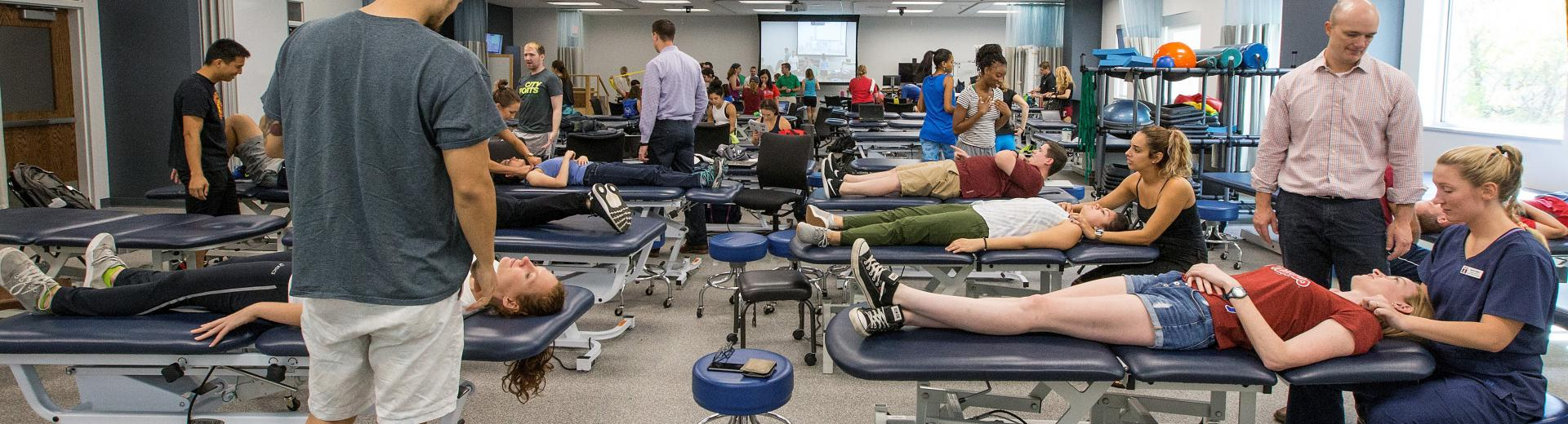 Physical therapy students practicing on patients
