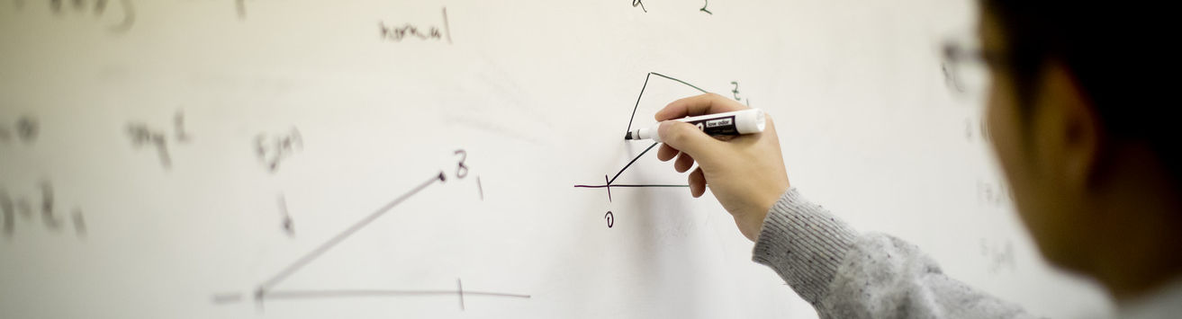 A student solves a math problem at a whiteboard in a classroom.