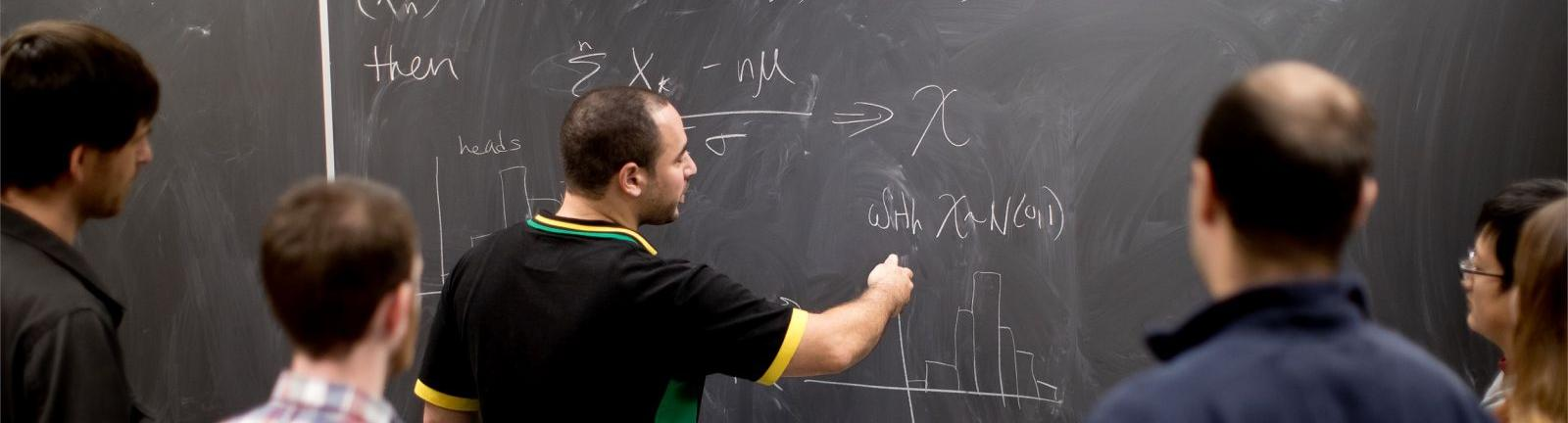Mathematics professor writing on a chalkboard with students gathered around