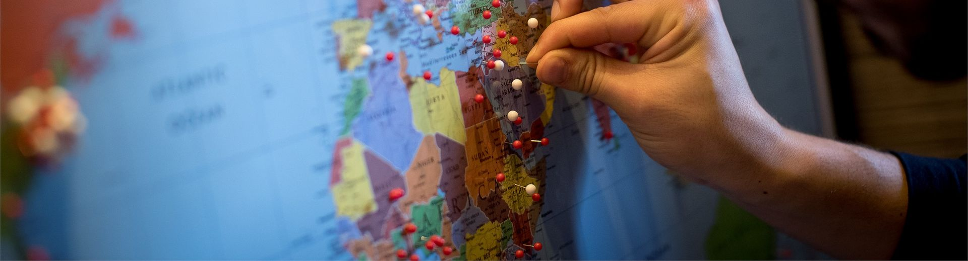 A man placing a pin in a world map.
