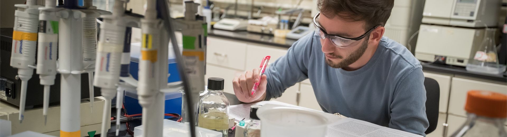 Temple student sitting over book, highlighter in hand, in a College of Science and Technology laboratory.