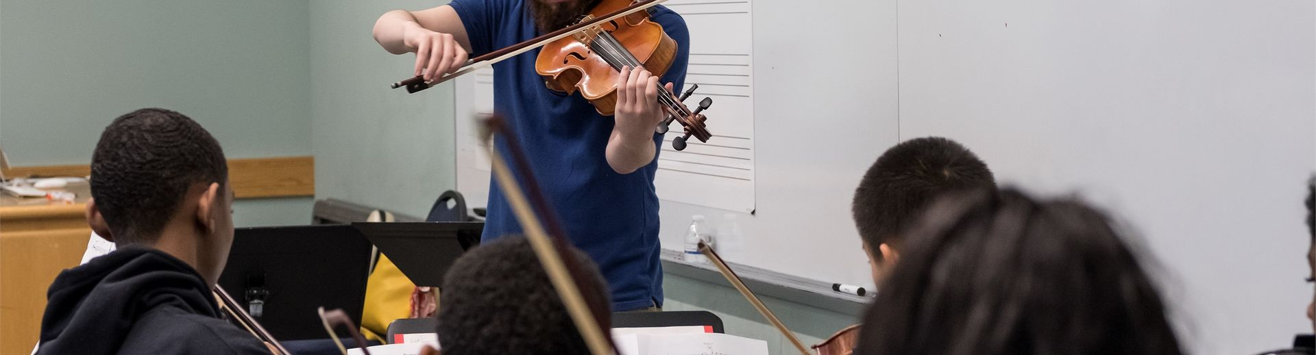 A violin teacher plays at the front of the class in front of young students.