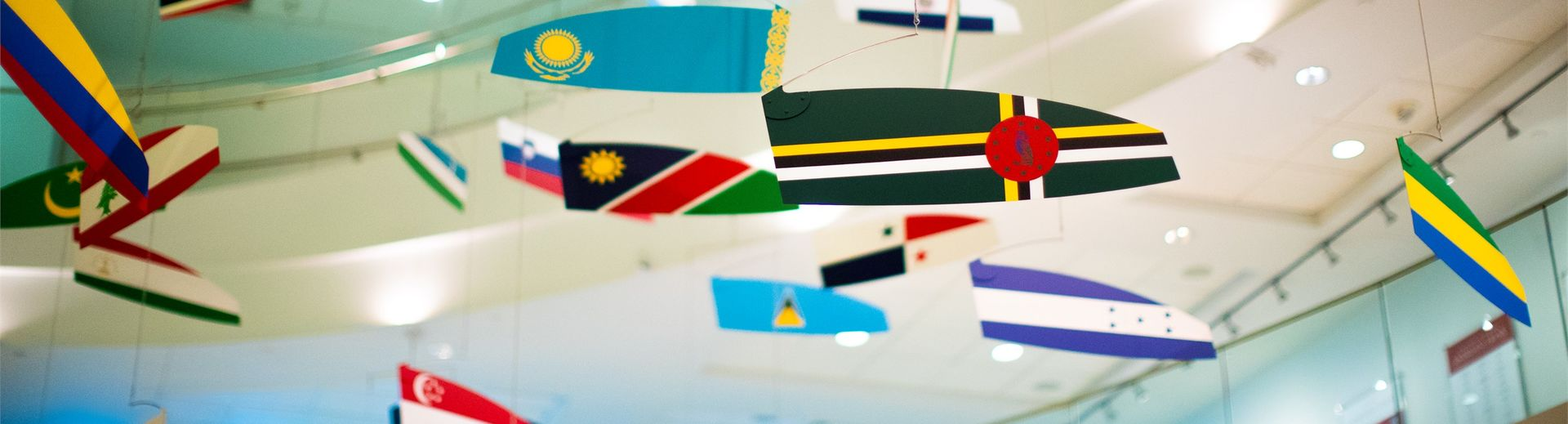 Colorful international flags hanging from ceiling in a business school lobby