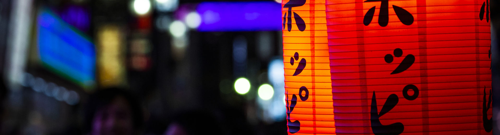 Brightly lit Japanese lanterns in Tokyo at night.