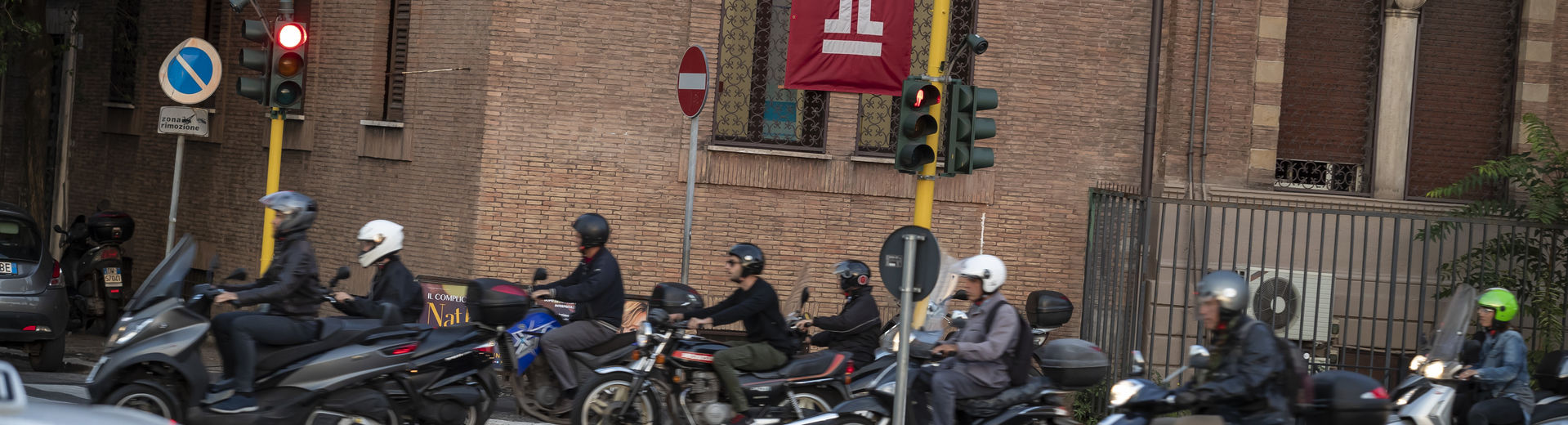 A group of people on motorcycles on an Italian street near Temple Rome.