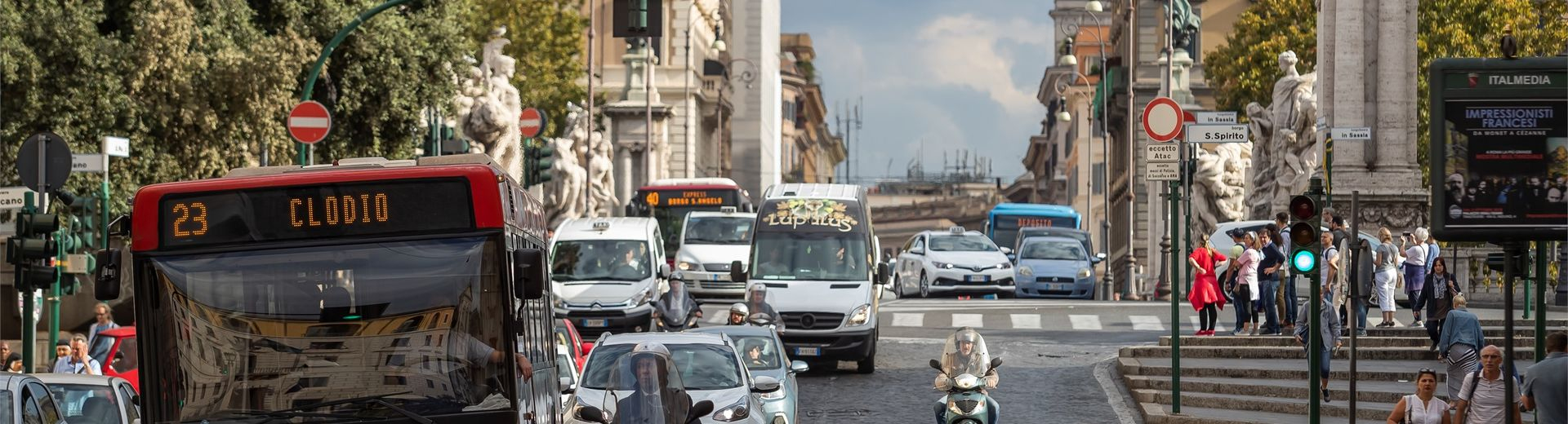 A bus, cars and scooters on a busy street in Rome, Italy.